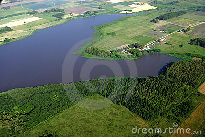 Lagoon and agriculture green fields