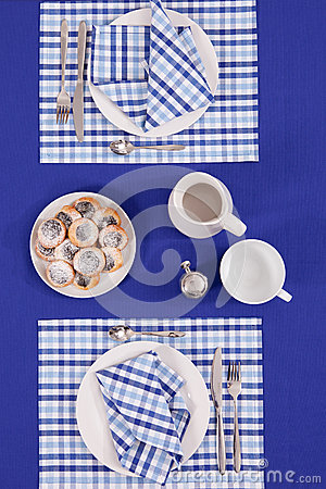 Laid table - fork and spoon laid on blue cloth and white plate