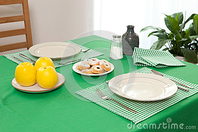 Laid table - fork and spoon laid on green cloth and white plate