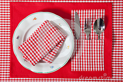 Laid table - fork and spoon laid on red cloth and white plate