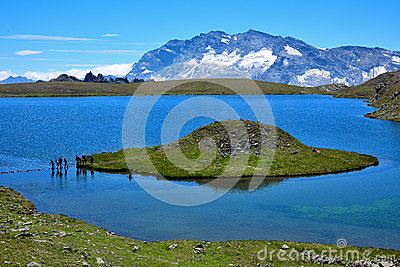 Lake with a strange shape island in the italian alps