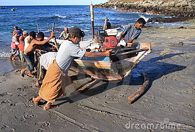Lamalera whalers pushing a boat Editorial Stock Image