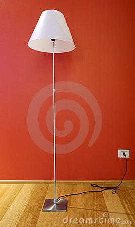 Lamp in hotel room, wooden floor and red wall