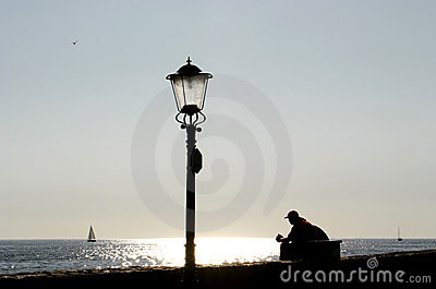 Lamp post and resting man