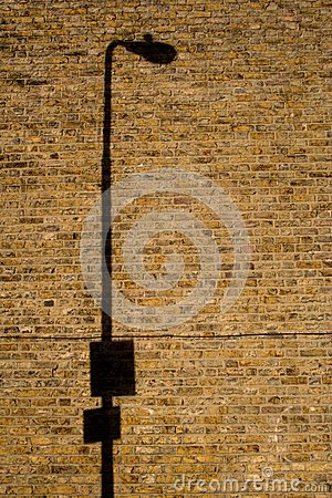Lamp post shadow on brick wall