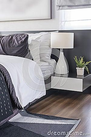 Lampada nera moderna sulla tavola bianca in camera da letto ...