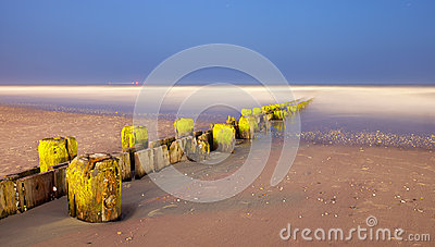 Landscape panorama of old pier posts on the beach