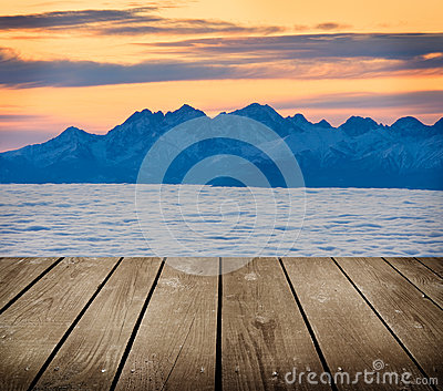 Landscape winter hill scene with fog and empty wooden deck table.