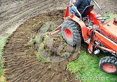 Tractor emoving turf