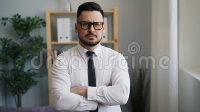 Langsames moton Porträt des ernsten Geschäftsmannes mit den gekreuzten Armen im Büro stock video footage