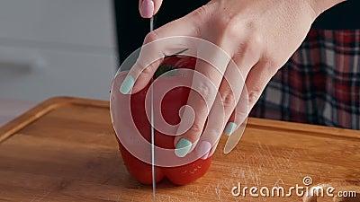 Langzame beweging van een vrouw met een mes dat in twee helften op een houten snijplaat niet-scherp rode peper heeft gesneden stock video