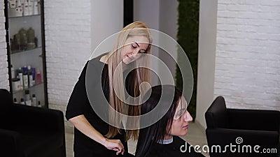 Langzame beweging van mooie blonde kapper die met haar kapper kampt, het natte, rechte haar van de vrouwelijke cliënt, die zich v stock footage
