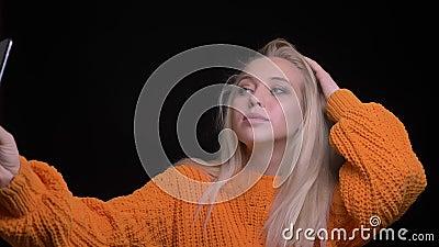 Lanzamiento del primer de la hembra caucásica bonita joven que toma selfies en el teléfono con el fondo aislado en negro metrajes