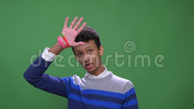 Lanzamiento del primer del var?n indio atractivo joven que agita hola mirando la c?mara con el fondo aislado en verde almacen de metraje de vídeo