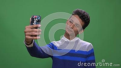 Lanzamiento del primer del var?n indio atractivo joven que tiene una llamada video en el tel?fono con el fondo aislado en verde almacen de metraje de vídeo