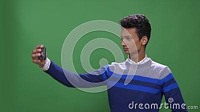Lanzamiento del primer del var?n indio atractivo joven que toma selfies en el tel?fono con el fondo aislado en verde metrajes