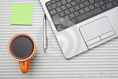 Laptop computer on desk with cup of tea