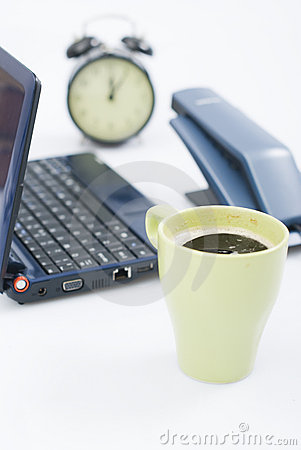 Laptop, desk-phone, clock and a coffe