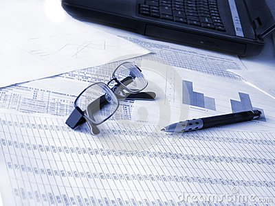 Laptop, glasses and pen on financial documents.