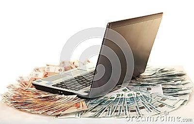 Laptop on large pile of bills five thousandth