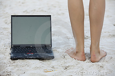 Laptop and legs on the beach