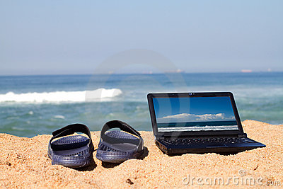 Laptop and sandals on beach