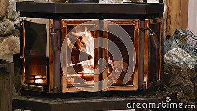 Lareira de fogão de madeira com corpo metálico e porta de vidro em casa com interior confortável video estoque
