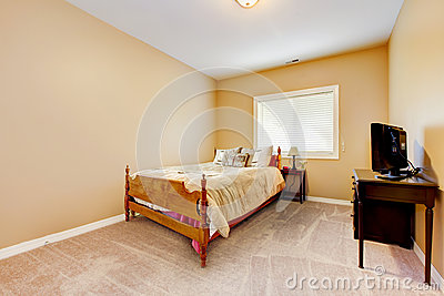 Large bedroom with yellow walls and beige carpet.