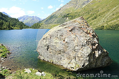 Large boulder in mountain lake