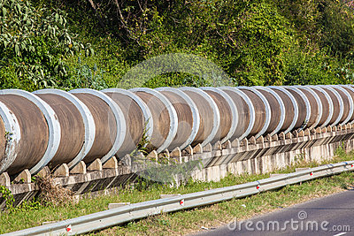 Section of a large concrete drain water liquid pipes above ground