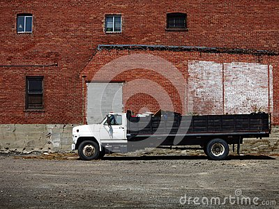Large Dumptruck and Brick Building Stock Photo