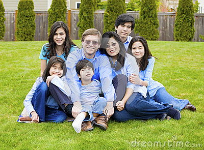 Large family of seven sitting together on lawn