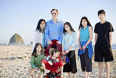 Large family of seven standing beach by ocean