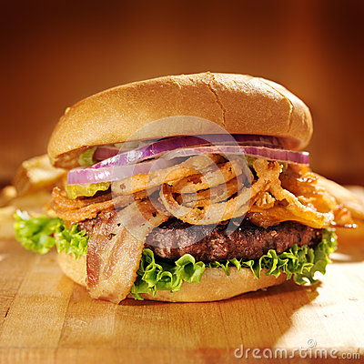 Large gourmet hamburger with fried onion straws.