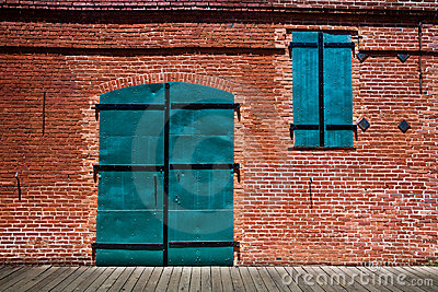Large green metal doors in old brick building