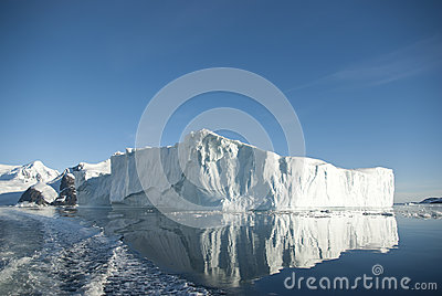Large iceberg and its reflection in the southern ocean on a summ