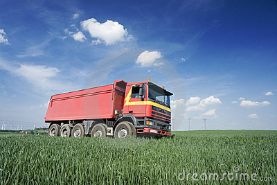 Large red truck in field
