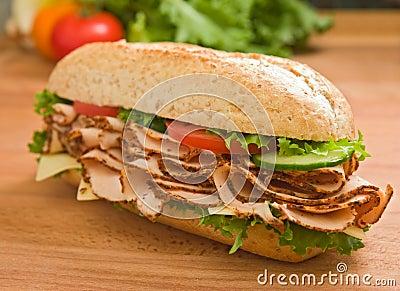 Large turkey breast sandwich on a wooden surface