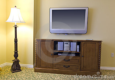 Large Tv Above Wooden Cabinet And Lamp Royalty Free Stock