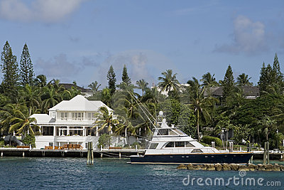 Large white home with boat in the tropics