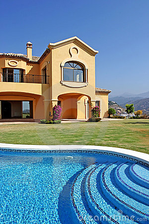 Large yellow sunny spanish villa with pool and blue sky