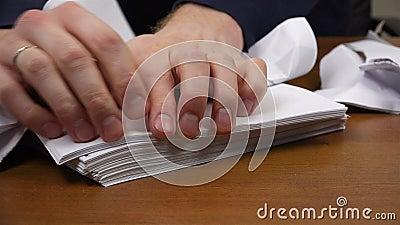 Las manos de los hombres rasgan documentos en pequeños pedazos almacen de metraje de vídeo