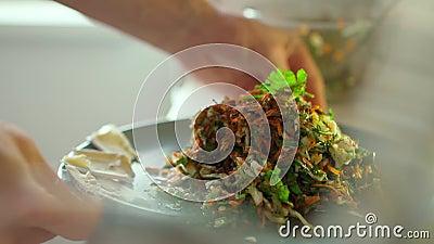 Las manos del hombre en cámara lenta se rotan el plato con ensalada vegetariana fresca almacen de metraje de vídeo