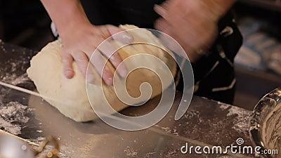 Las manos del panadero amasan la pasta metrajes