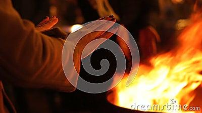 Las manos que se calientan de la gente acercan al fuego en el festival de la calle, celebración de las vacaciones de invierno almacen de video