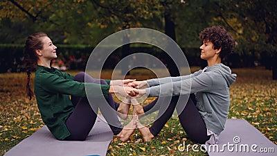 Las muchachas atractivas están haciendo ejercicios de la yoga en los pares que llevan a cabo las manos y que ponen los pies junta almacen de video