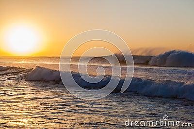 Las olas oceánicas lavan a chorro salida del sol