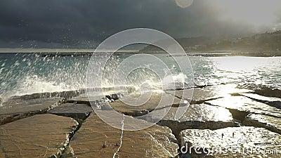Las ondas enormes se rompen en las nubes dramáticas y el sol de los acantilados costeros metrajes