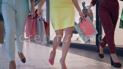 Las piernas de las mujeres elegantes del comprador acometen en descuentos estacionales en boutique de la moda y llevan la porción almacen de video