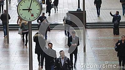 Lasso di tempo dei pendolari che camminano dopo gli orologi, Canary Wharf, Londra stock footage